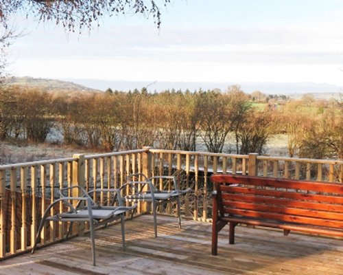A deck with seating overlooking meadow view.