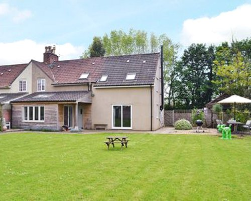 An exterior view of the Sharpham Road cottage with a picnic seat on the well maintained lawn.