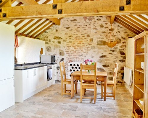 An open plan kitchen with dining area and vaulted ceiling.