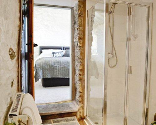 A bathroom with a shower alongside bedroom.