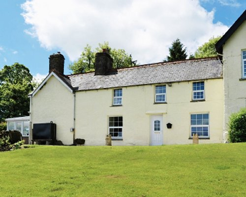 Scenic exterior view of Groudd Hall Cottage surrounded by wooded area.