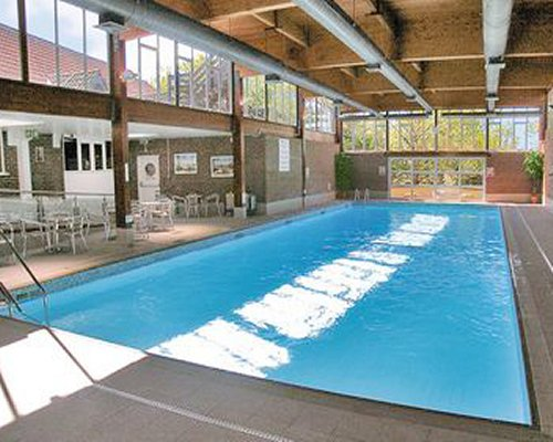 An indoor swimming pool with patio furniture and an outside view.