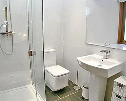 A bathroom with shower stall and single sink vanity.
