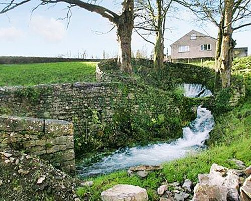 A scenic landscape with a flowing stream alongside a unit.