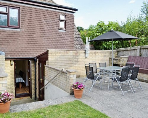 Outdoor dining and sunshade alongside a unit.