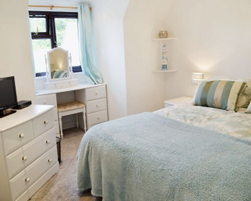 A well furnished bedroom with a television and outside view.