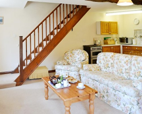 A well furnished living with an open plan kitchen alongside a stairway.