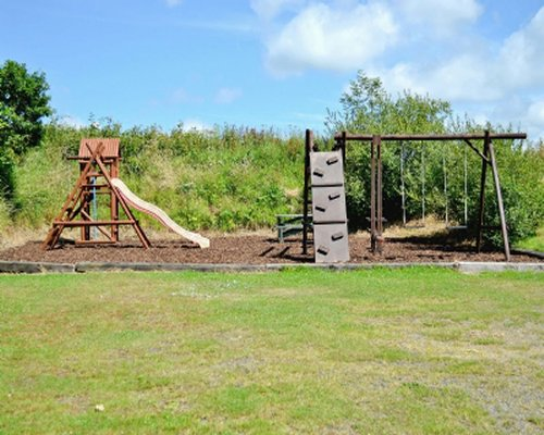 An outdoor playscape alongside the shrubs.