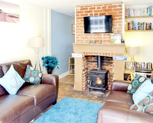 A well furnished living room with a television fire in the fireplace and bookshelf.