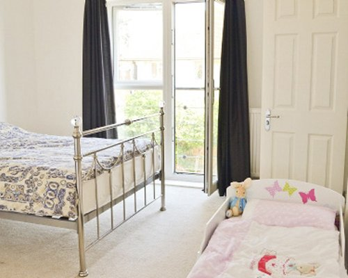 A well furnished bedroom with a baby crib.