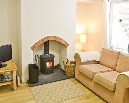 A well furnished living room with television,fire in the fireplace and pull out sofa.