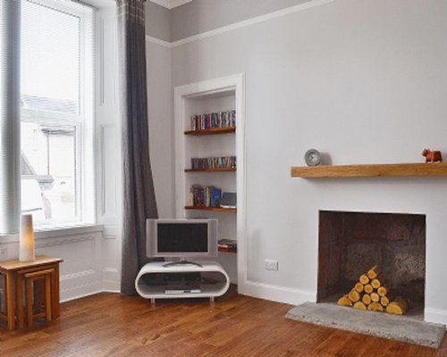 A room with television fireplace and a bookshelf.