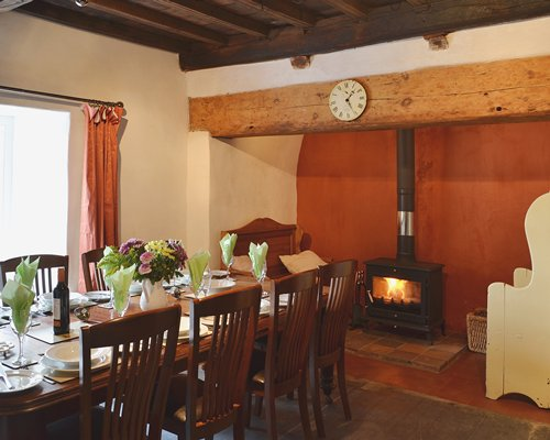 A well furnished dining area with a fire at the fireplace and an outside view.