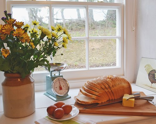 A view of bread cheese and egg on a table with a flower vase.