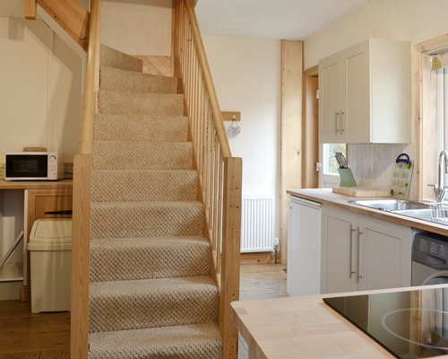 An open plan kitchen with a stairway.