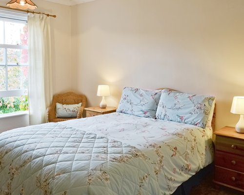 A well furnished bedroom with two lamps and an outside view.