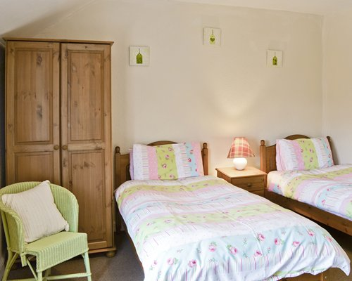 A well furnished bedroom with two twin beds and patio furniture.