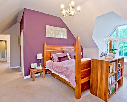A well furnished bedroom with a bookshelf and outside view.