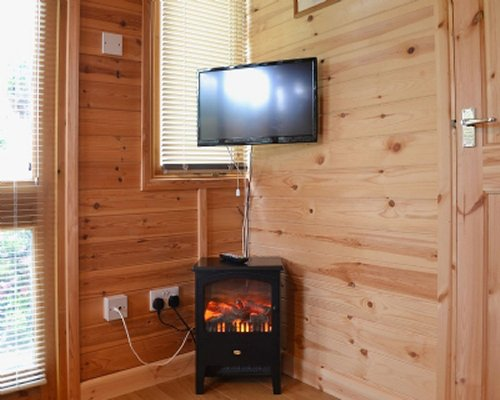 A wood paneled view of living area with fireplace and television.