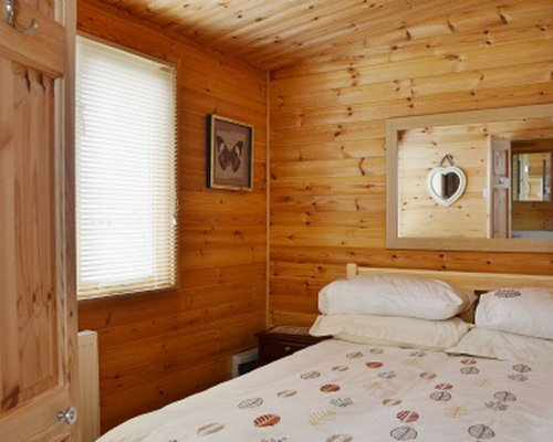 A wood paneled bedroom with a window.