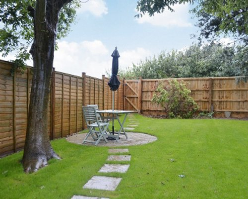 A fenced in yard with patio table seating.