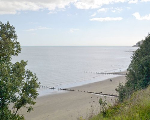 A view from hillside of beach and water view.
