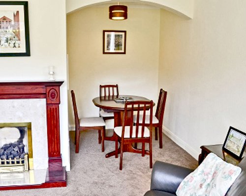 A well furnished living room with a fireplace and dining table.