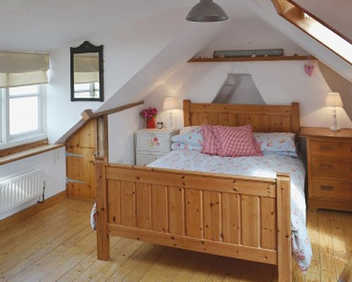 A well furnished bedroom in the vaulted ceiling.