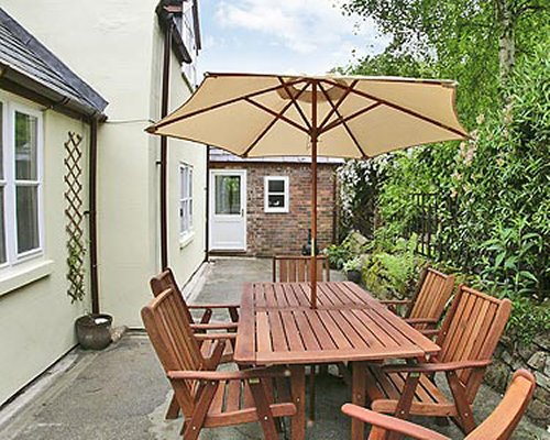 An outdoor patio with sunshade alongside a cottage unit.