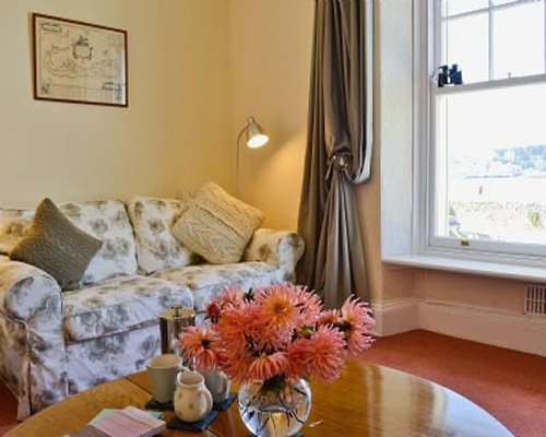 A well furnished living room with a sofa flower vase on a table and outside view.