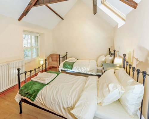 A bedroom with twin beds high ceiling skylight and a window.