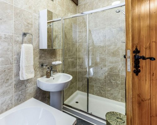 A bathroom with sink and shower stall.