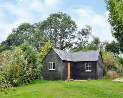 Scenic exterior view of the Walnut Tree Cottage surrounded by wooded area.