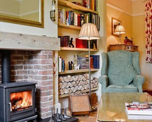 A well furnished living room with a fire in the fireplace and bookshelf.