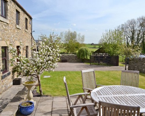 A large back patio area with table seating and countryside views.
