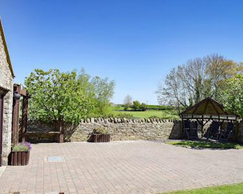 A large back patio area with stone walls and countryside views.
