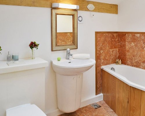 A bathroom with a single sink vanity bathtub and shower.