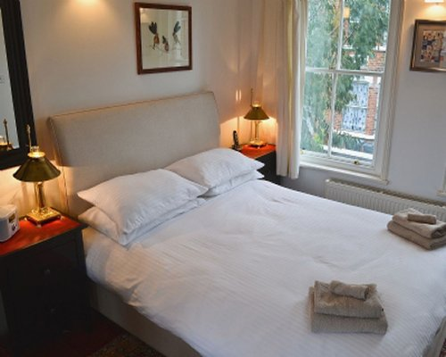 A furnished bedroom with a large bed and a window.