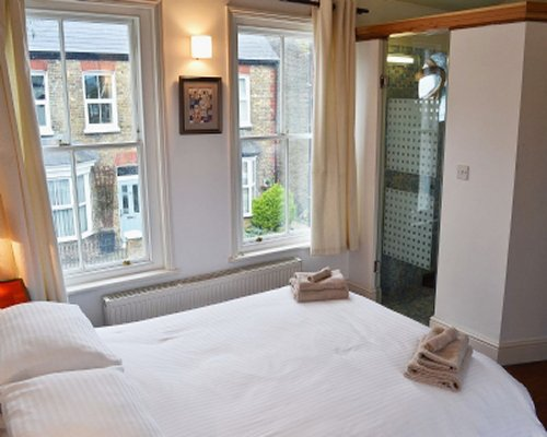 A furnished bedroom with a large bed and windows.