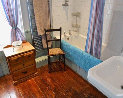 A bathroom with wood floors and bathtub.