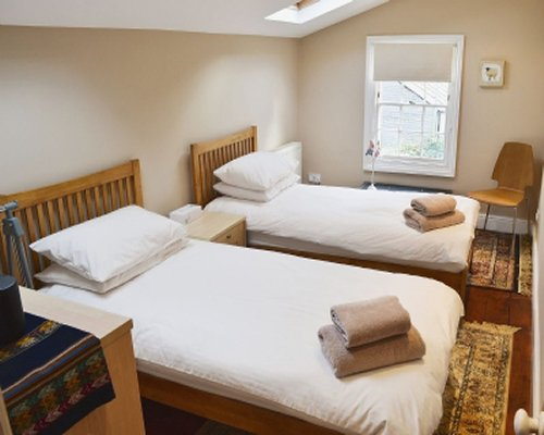 A bedroom with twin beds and a window and a skylight.