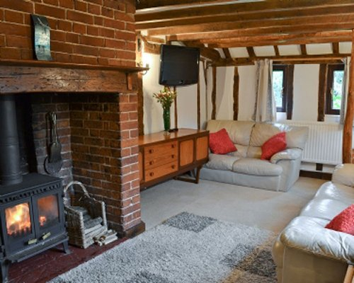 A well furnished living room with a sofa television and fire in the gas log fireplace.