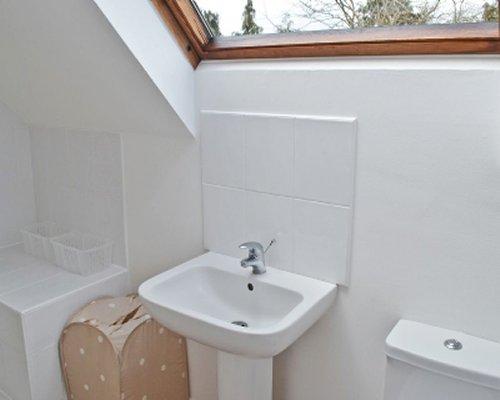 A bathroom with sink and a skylight.