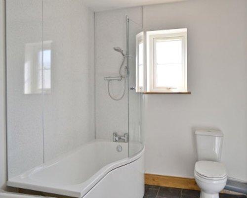 A bathroom with a bathtub and shower.