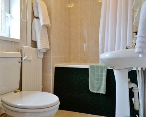 A bathroom with a pedestal sink and bathtub.