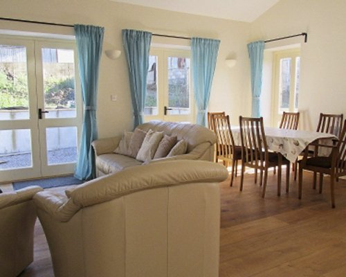 A well furnished living room with dining area and patio.