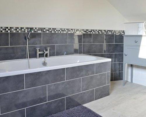 A bathtub set in granite tile.