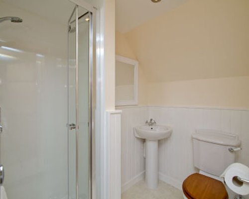 A bathroom with stand up shower and single sink vanity.