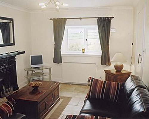 A well furnished living room with a sofa television fireplace and outside view.