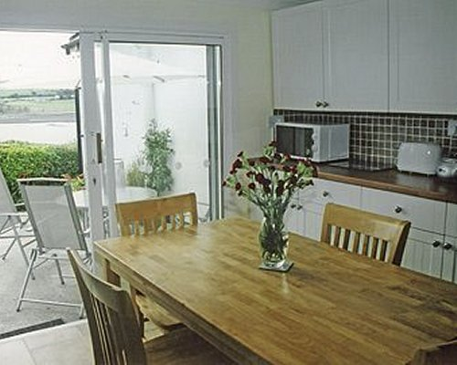An open plan kitchen with dining area and outdoor patio.